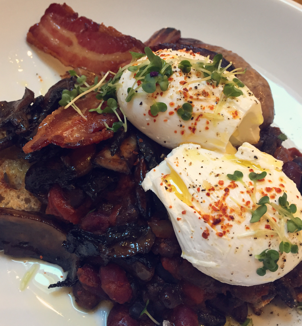 black mocha brighton review - two poached eggs sit neatly atop a pile of beans, mushrooms and bacon on sourdough. Delicious.