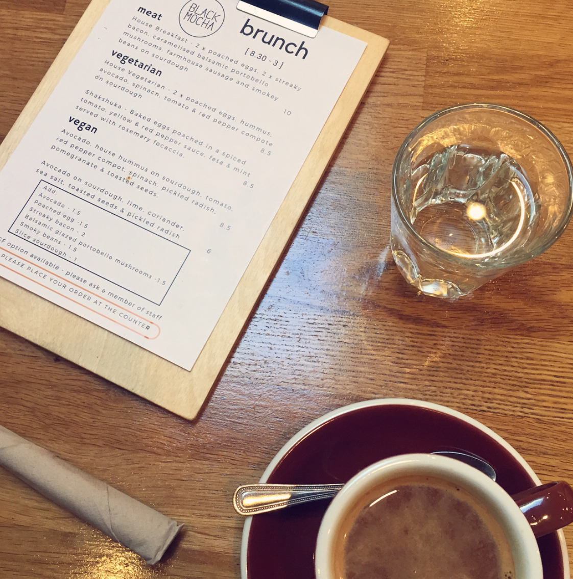 tabletop view at black mocha brighton, including their famous 'black mocha' beverage, a glass of water and the menu