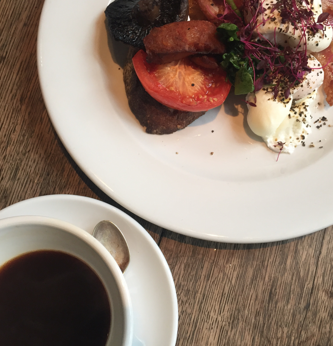 Cafe rust review - veggie breakfast, with tomato, mushrooms and poached eggs in picture. Black coffee pictured to bottom left of image