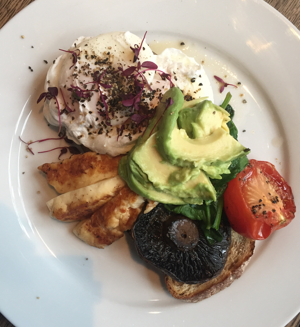 cafe rust review – full plate view of veggie breakfast, including poached egg, halloumi, grilled tomato, sliced avocado, spinach, mushroom and fresh bread