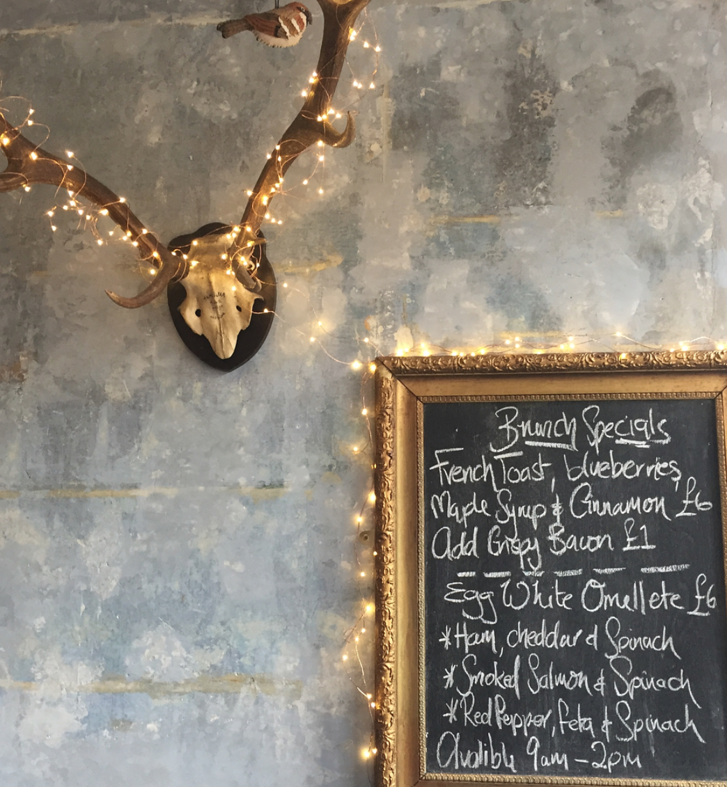 cafe rust interiors – a deer skull with antlers is illuminated by the fairy lights wound around it, which descend to the framed blackboard menu detailing the brunch specials