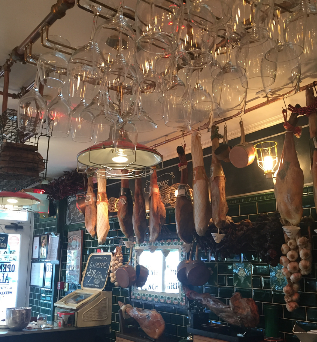 cured hams hang from the ceiling in spanish-styled Market Restaurant, hove